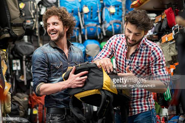 Men looking at backpacks in sports store