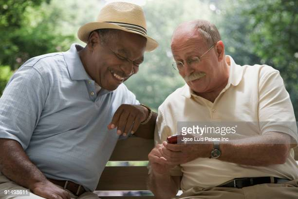 Men looking at cell phone on park bench