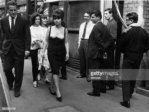 Men looking on as a woman walks down the street wearing a topless dress August 1964 P018319