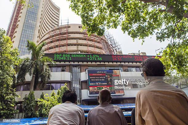 Men looks up at an electronic screen displaying stock figures at the Bombay Stock Exchange in Mumbai India on Tuesday June 7 2016 Indian central bank...