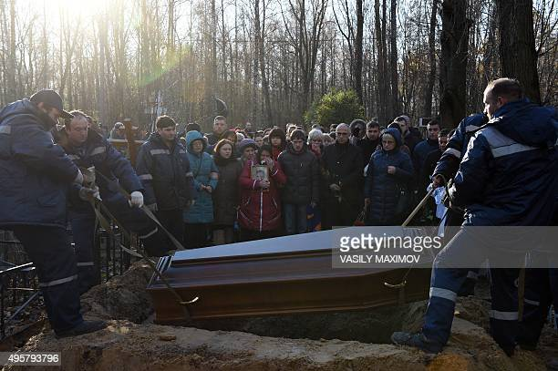 Men lower the coffin of Alexei Alexeyev a victim of the Russian MetroJet Airbus A321 crash into the grave during his funeral at a cemetery in St...