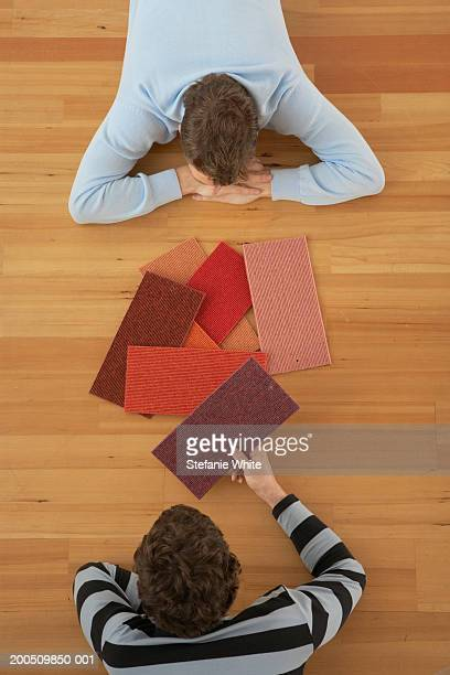 Men lying on floor looking at carpet samples, overhead view