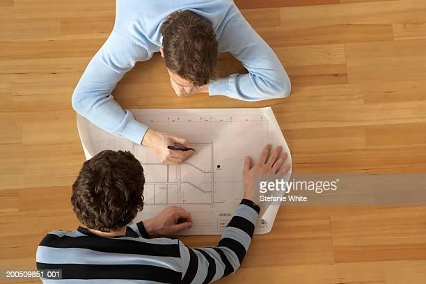 Men lying on floor looking at plans, overhead view