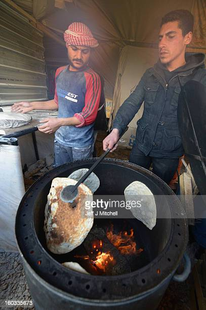 Men make bread as Syrian refugees go about their daily business in the Za'atari refugee camp on January 29 2013 in Mafraq Jordan Record numbers of...