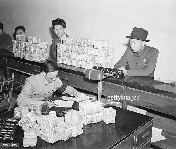 Men make large deposits of yuan at a bank in Kunming, China.