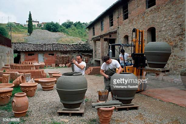 Men make large pots at a pottery factory in Tuscany