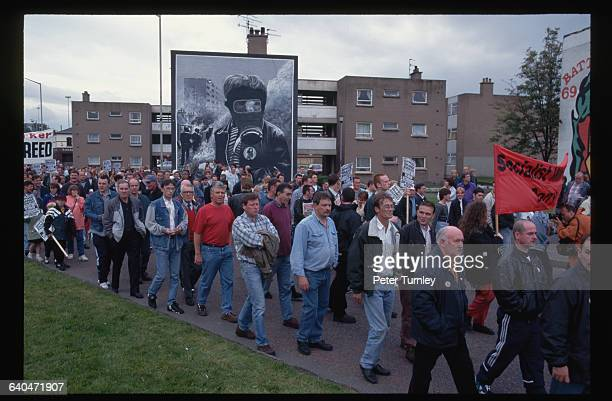Men march protesting the sectarian divisions caused by the annual march of the Apprentice Boys through the largely Catholic area of Bogside The...