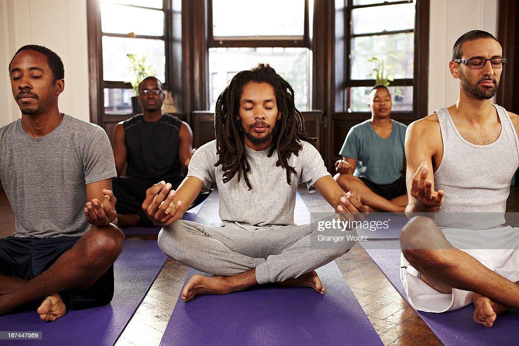 Men meditating in yoga class : Stock Photo