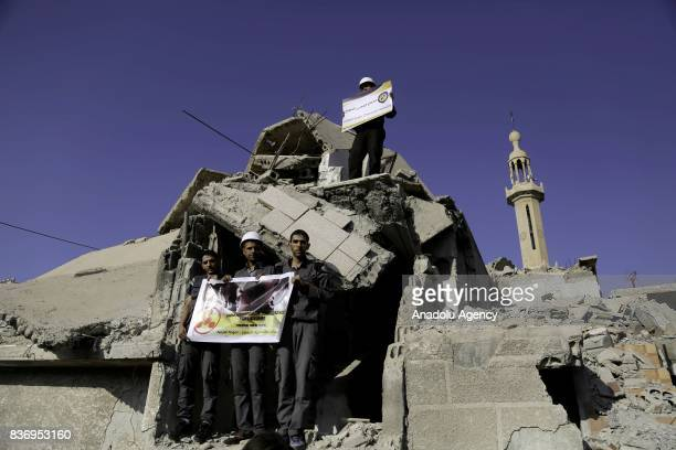 Men members of Syrian civil defense organization White Helmets hold a photo of a person and a placard who lost his life in chemical attack that in...