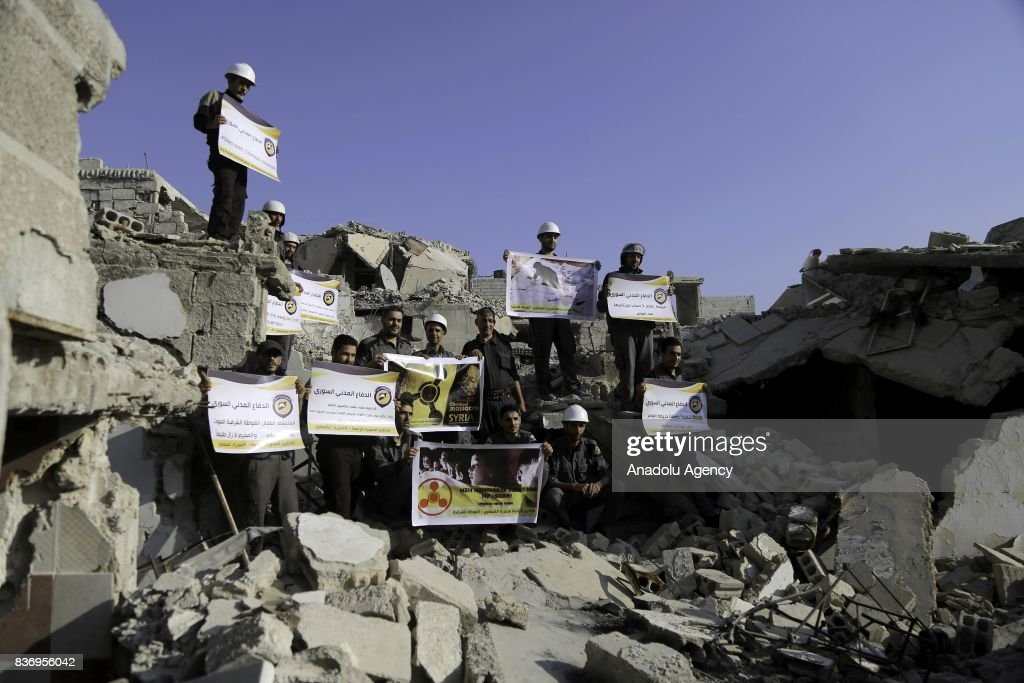 Men, members of Syrian civil defense organization, White Helmets hold a photo of a person and a placard who lost his life in chemical attack that in the Eastern Ghouta region of Damascus, Syria on August 22, 2017. It is the 4th anniversary of chemical weapons attack near countrysides of Zamalka that Assad Regime's forces carried out.