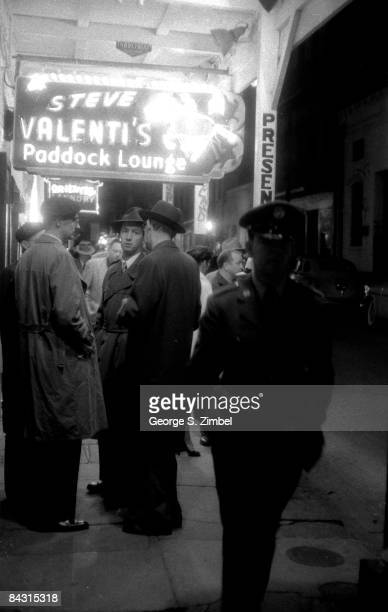 Men mill about outside Steve Valenti's Paddock Lounge at night the jazz hotspot located on New Orleans' Bourbon Street 1955 United States
