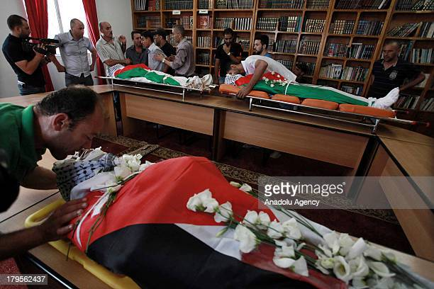 Men mourn over the bodies at the funeral of three Palestinians on August 262013 at the Qalandia Refugee Camp near Ramallah Palestine The 3...