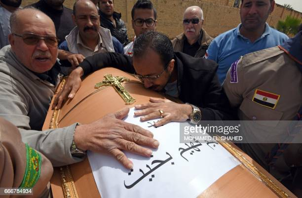 Men mourn over the coffin of one of the victims of the blast at the Coptic Christian Saint Mark's church in Alexandria the previous day during a...