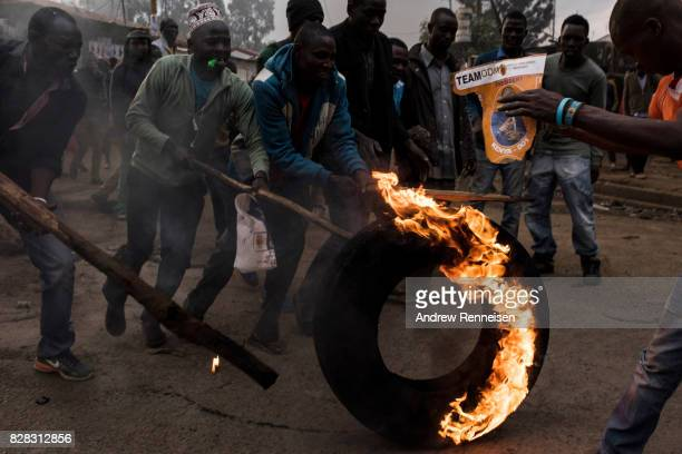 Men move a burning tire during a protest in Kibera Kenya's biggest slum on August 9 2017 in Nairobi Kenya The protest started after police allegedly...