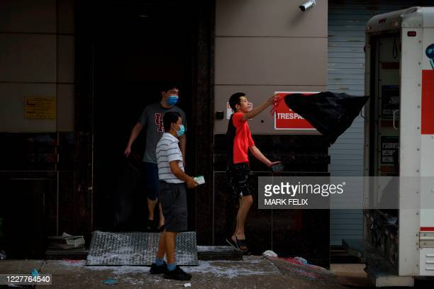 Men move bags into a U-Haul truck outside of the Chinese consulate in Houston on July 24 after the US State Department ordered China to close the...