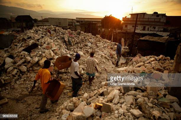Men move through collapsed market place in search of salvageable building materials along the Grand Rue one of the oldest business districts in the...
