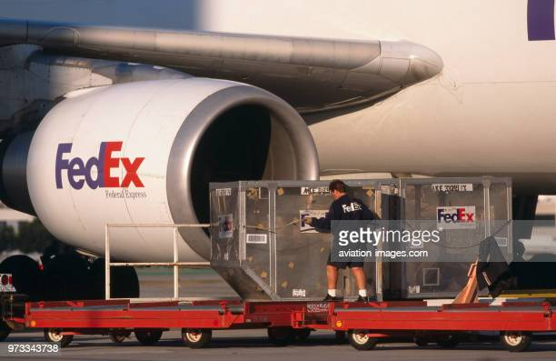 men moving LD3 containers on trolleys with CF680 engineintake of a FedEx Airbus A300600 freighter