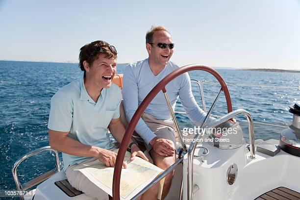 Men navigating yacht