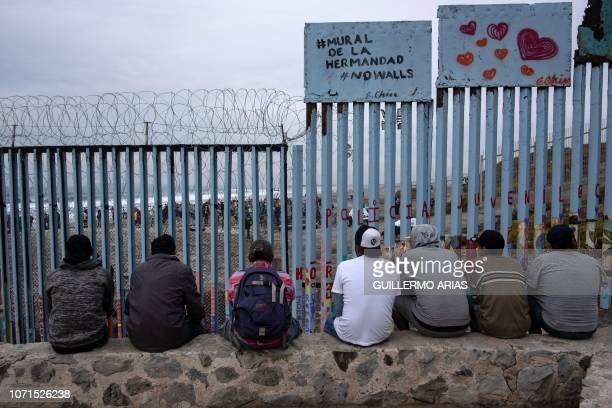 TOPSHOT Men next to a sign reading Mural of brotherhood watch from Playas de Tijuana Baja California state Mexico through the MexicoUS border fence...