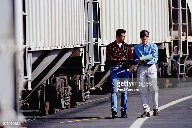 Men Next to Train Checking Paperwork