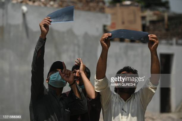 Men observe an annular solar eclipse through XRay films in Islamabad on June 21 2020