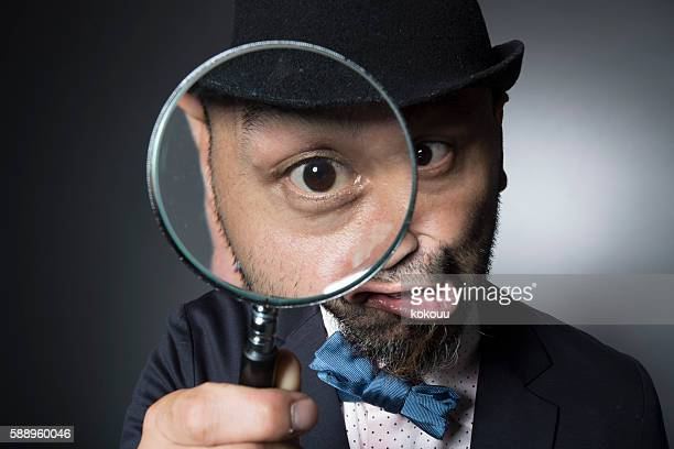 Men observing the eyeball in the magnifying glass