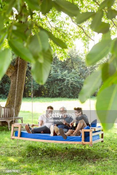 men of a family sitting on a swing bed ing the garden, talking, using digital tablet - adults only stock pictures, royalty-free photos & images