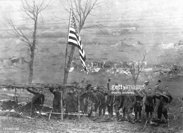 Men of Battery D, 105th Field Artillery, smile and wave their helmets, underneath an American flag, upon firing the last shot before the Armistice's...
