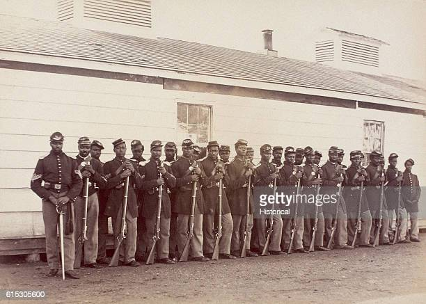 Men of Company E of the 4th United States Colored Troops stand outside their barracks at Fort Lincoln
