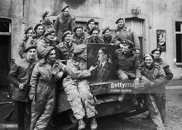 Men of the British 7th Armoured Division with a looted painting of Adolf Hitler in Gemon Germany April 1945