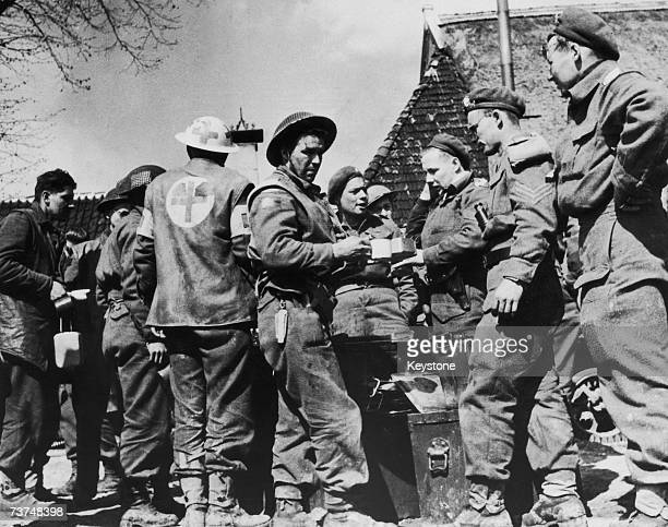 Men of the Canadian infantry regiment relax with tea and a hot meal after capturing the Dutch city of Groningen during World War II April 1945