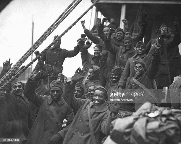 Men of the famous 369th Infantry smile and wave as they arrive in New York City 1919 The 369th formerly the 15th New York National Guard Regiment was...