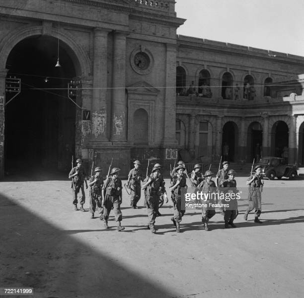 Men of the First Battalion of the Wiltshire Regiment leaving City Police headquarters on a peacekeeping patrol after communal riots in Amritsar...