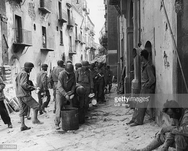 Men of the first US infantry division line up in the street holding utensils as they wait to eat a meal from a large pot Troina Sicily The Allied...