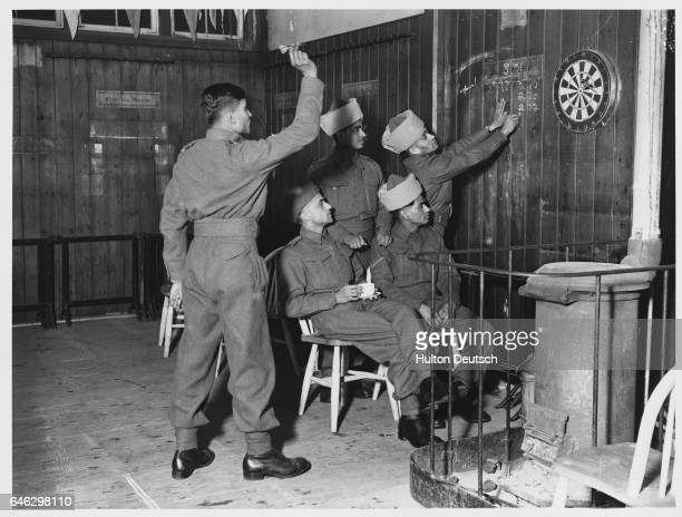 Men of the Indian Auxiliary Corps playing darts in the recreation room of the educational institution where they are based 1940