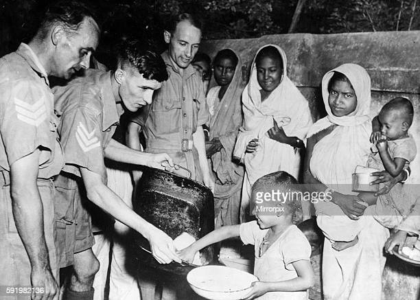 Men of the Royal Air Force feeding local children in tre Indian famine areas at an RAF station in Bengal India during the Second World War December...