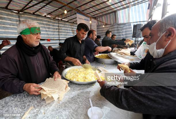 Men offer food to Iranian Shiite Muslim pilgrims at the IranianIraqi Mehran border as they head towards the central Iraqi shrine city of Karbala on...