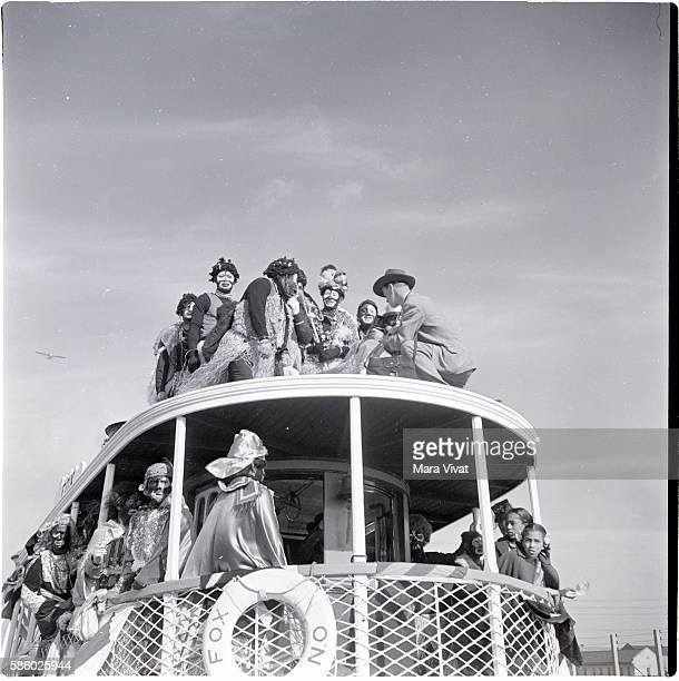 Men on a ferry for a Mardi Gras event are in blackface and dressed as African tribesman New Orleans Louisiana circa 1950