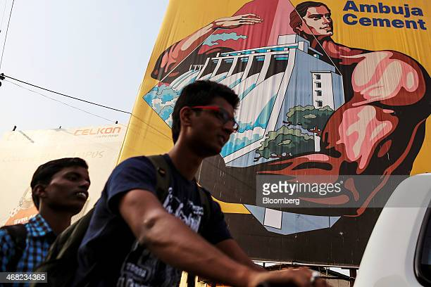 Men on a motorbike pass by an advertisement for Ambuja Cements Ltd in Nashik India on Monday Feb 03 2014 India's consumer price index figures for...