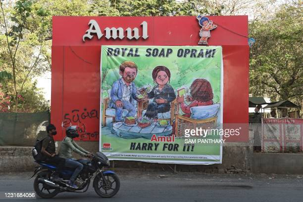 Men on a motorbike ride past a billboard of Indian dairy cooperative society Amul depicting Britain's Prince Harry , Duke of Sussex and his wife...