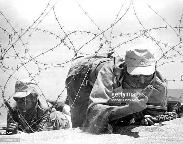Men on active military duty scrawling on the ground looking through barbed wire at the enemy in a scene from the film 'Play Dirty' 1969