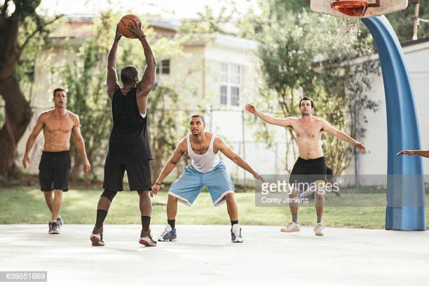 Men on basketball court playing basketball, defending hoop