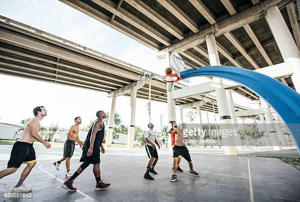 Men on basketball court watching basketball go through hoop