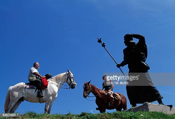 Men on horseback near the bronze pilgrim statue near Alto de San Roque on the Way of St James of Compostela Galicia Spain