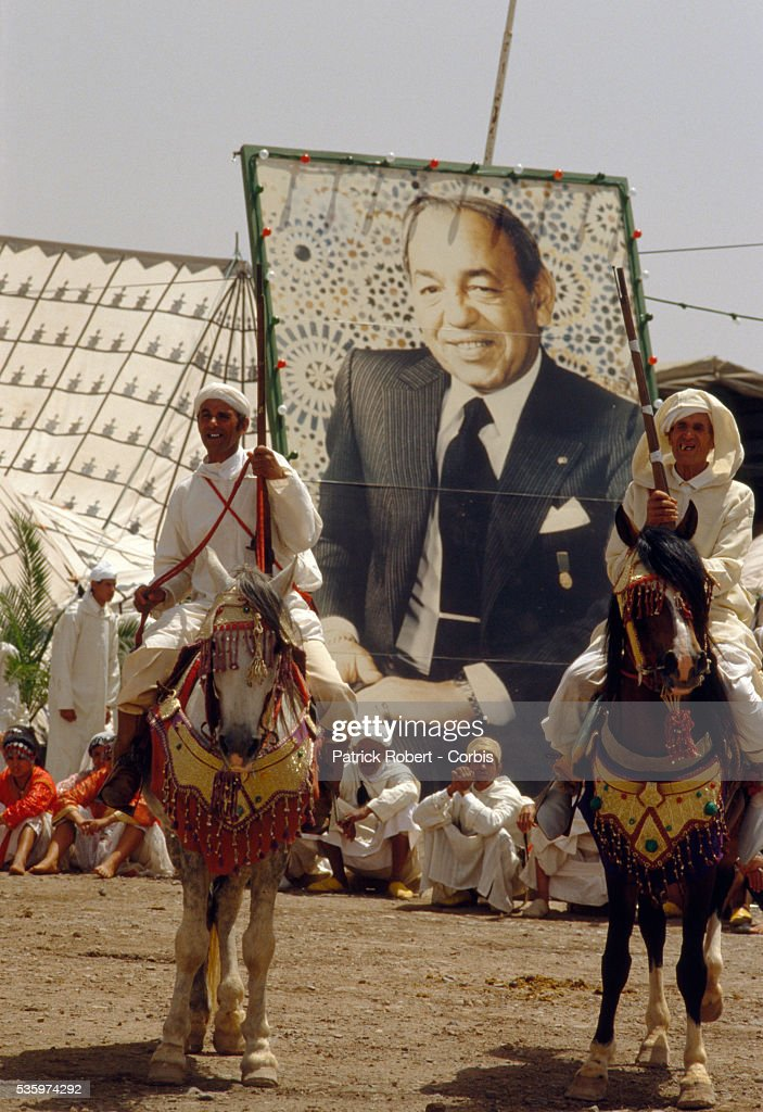 Men on horseback prepare to celebrate wedding of Princess Lalla Asmaa, daughter of Hassan II, King of Morocco. Spectators sit before a large poster of King Hassan.