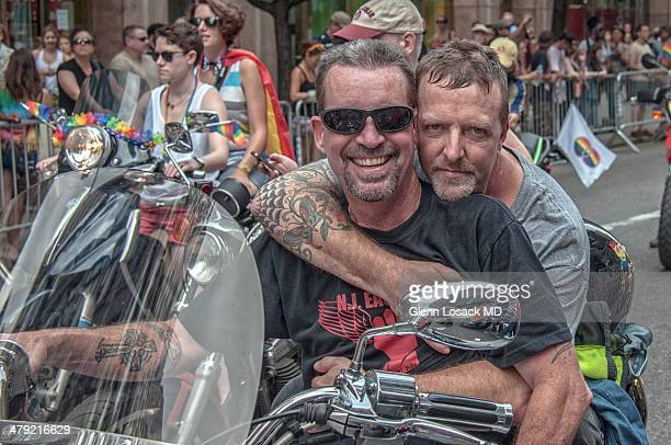 Men on motorcycle one has arm around the driver snuggling close Gay men on their motorbikes open the Gay parade in Manhattan