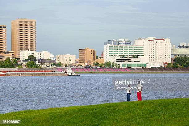 men on riverbank with city beyond - timothy hearsum fotografías e imágenes de stock