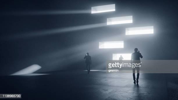 mannen aan de telefoon wandelen in donkere, futuristische straat - onwetendheid stockfoto's en -beelden