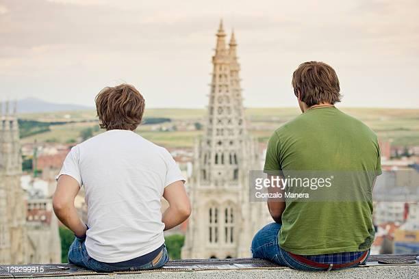 Hombres en pared con vista al paisaje urbano