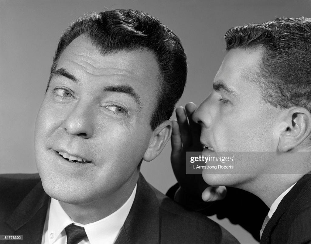 2 Men One Whispers In Others Ear Gossip Secret Listening Sharing Rumor. : Stock Photo